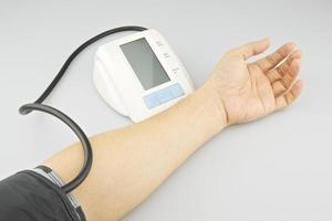 Mann testet den Blutdruck am linken Arm foto