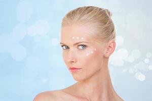blonde Frau testet Salbe auf ihrem Gesicht foto