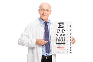 reifer Optiker, der auf einen Sehtest zeigt foto