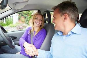 Teenager-Mädchen, das Fahrprüfung mit Prüfer besteht foto