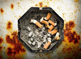 Aschenbecher mit Zigarettenstummeln foto