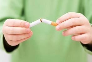junges Mädchen bricht eine Zigarette foto