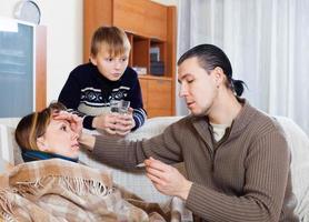 Mann, der die Temperatur der kranken Frau misst foto