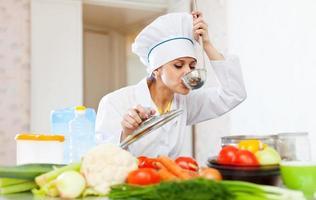 kochen in weißer Uniform testet Suppe aus der Pfanne foto