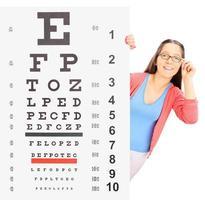 Teenager-Mädchen mit Brille, die hinter Sehtest steht foto