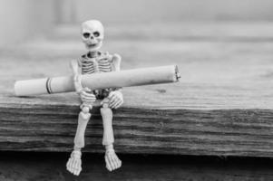 Skelette mit Zigarette sitzen auf Holztisch, selektiver Fokus foto