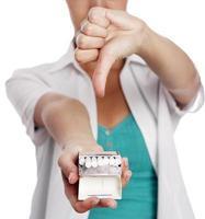 Frau hält Zigaretten und zeigt Daumen nach unten foto