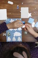 kleines Mädchen, das Weihnachtskarten macht foto