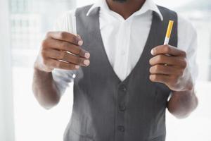 Gelegenheitsgeschäftsmann, der Zigaretten hält foto