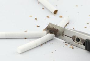 Nahaufnahme des Schneiders, der die Zigarette schneidet foto