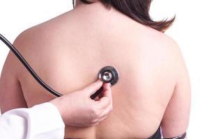 junge Frau, die von ihrem Hausarzt auf Lungenentzündung untersucht wird