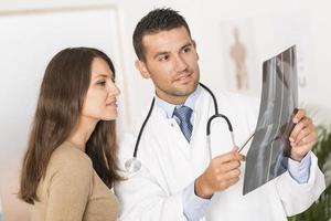 Arzt zeigt dem Patienten das Röntgenergebnis foto