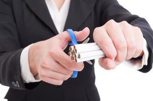 Frau, die eine Hand von Zigaretten mit einer Schere oder einer Schere schneidet foto