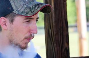 Mann atmet dampfenden Nebel aus dem Mund aus foto