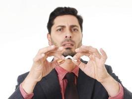 junger hispanischer attraktiver Mann, der Zigarette bricht in Rauchentwöhnungsauflösung foto