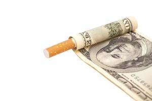 Zigarette und einhundert Dollarschein auf weißem Hintergrund foto