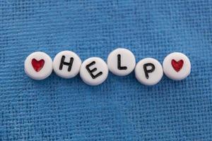 Hilfe mit Perlen auf Leinwand geschrieben foto