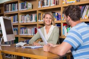 Schüler bekommen Hilfe vom Tutor in der Bibliothek foto