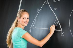 hübscher junger Lehrer, der an die Tafel schreibt foto