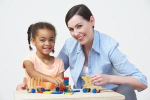 Lehrer und Vorschulkind spielen mit Holzhaus foto