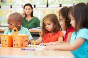 Gruppe von Kindern im Grundschulalter im Kunstunterricht mit Lehrer foto