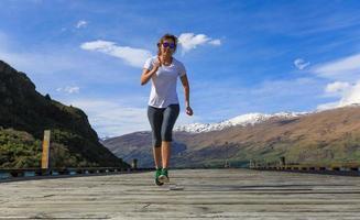 junge erwachsene Frau läuft auf Pier foto