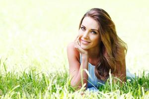 junge Frau im blauen Kleid, das auf Gras liegt foto