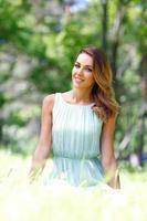 junge Frau im blauen Kleid sitzt auf Gras foto
