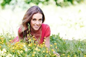 junge Frau im roten Kleid, das auf Gras liegt foto
