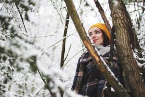 Porträt einer jungen Frau im verschneiten Wald foto