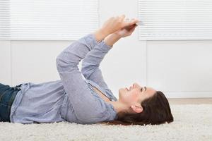 Frau mit digitaler Tablette beim Liegen auf Teppich
