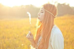 Hippie Frau, die Blume bläst foto
