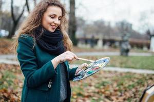 junge Frau, die in Staffelei auf dem Parkhintergrund zeichnet