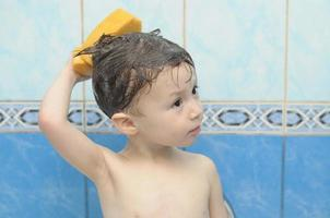 Junge wäscht seinen Kopf mit einem Schwamm foto