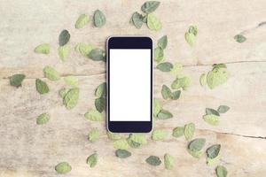 leerer Smartphonebildschirm mit Blättern auf Holztisch, verspotten foto