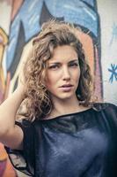 junge Stadtfrau vor der Grafitti-Wand foto