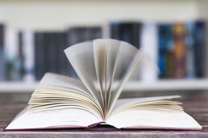 geöffnetes Buch vor dem Bücherregal