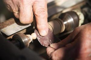 alter Zimmermann, der mit Holz arbeitet, getöntes Foto