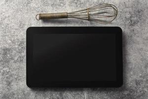 digitales Tablet mit Schneebesen und antikem Besteck auf Grunge-Bac