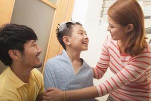 Mutter und Vater trocknen ihren Sohn ab