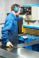 Arbeiter, der Guillotinenschermaschine bedient foto