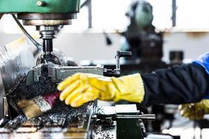 Arbeiter, der die Bohrmaschine in der Fabrik bedient