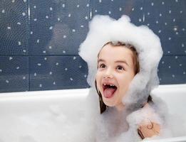 überraschtes kleines Mädchen, das in einem Bad sitzt foto