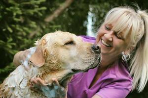 Frau, die ihren Hund wäscht foto