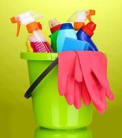 Eimer mit Reinigungsgegenständen auf grünem Hintergrund foto
