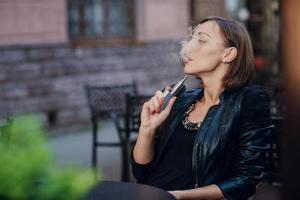 schöne glamouröse brünette rauch elektronische zigarette foto