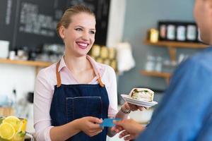 Kellnerin, die Kunden im Café bedient foto