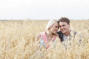 glückliches liebendes junges Paar, das inmitten des Feldes sitzt foto