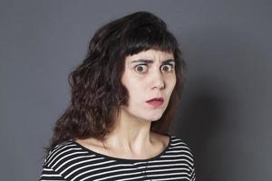 ängstliche junge brünette Frau, die erschrocken aussieht foto