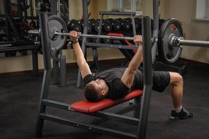 junger Mann, der Bankdrücken-Training im Fitnessstudio macht